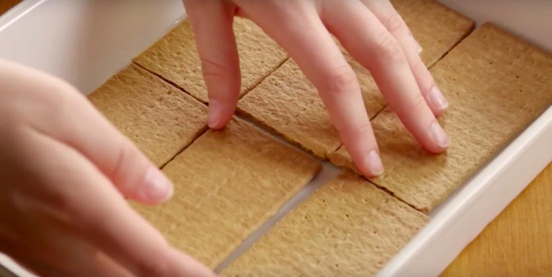 Elle étale des biscuits Graham dans un plat et nous montre comment créer un gâteau éclair en un temps record