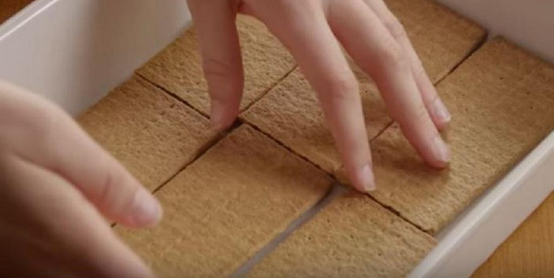 Elle place des biscuits graham dans le fond d'un moule. La couche qui suit est tout simplement divine.