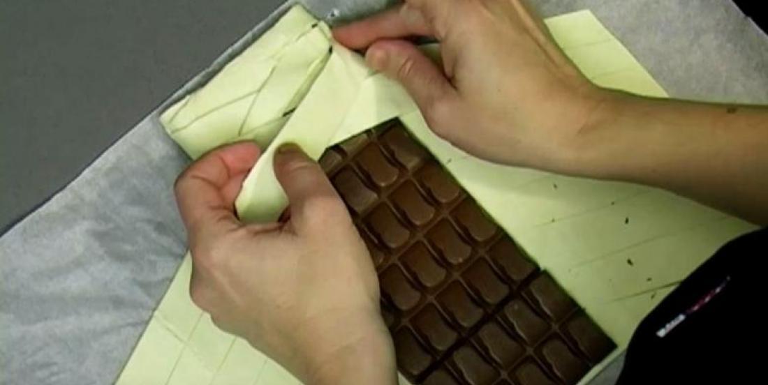 Il prend une tablette de chocolat et l'enroule dans de la pâte feuilletée