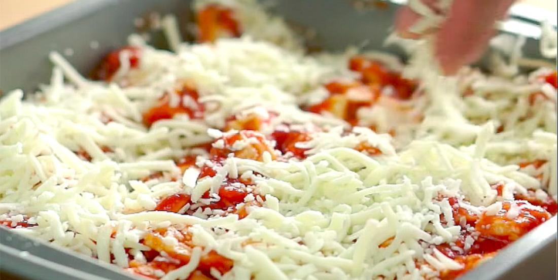 Dans un plat qui va au four, elle dépose du poulet, de la sauce tomate et du fromage et elle crée un repas délicieux